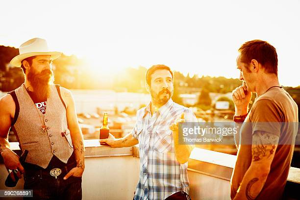 Man in discussion with friends on rooftop