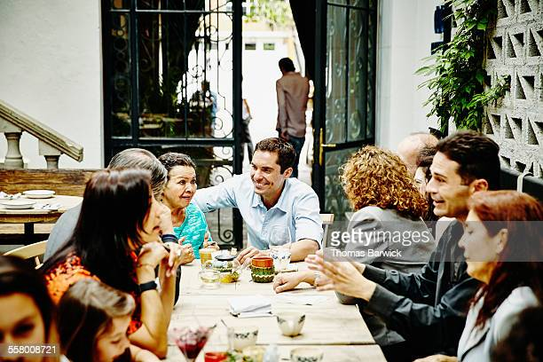 Man in discussion with mother during family dinner