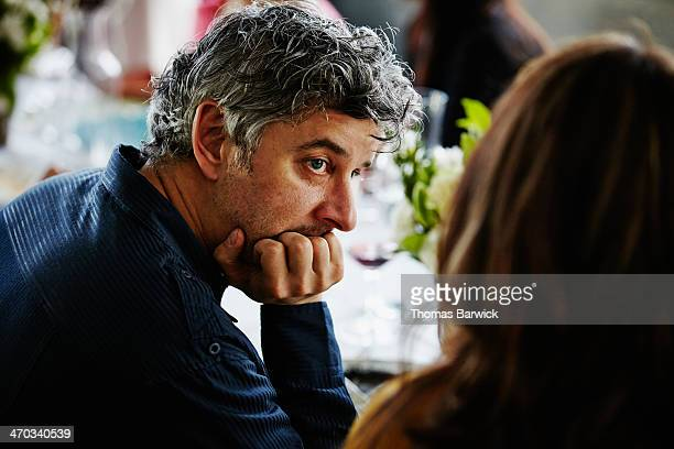 Man in discussion with wife at dinner party