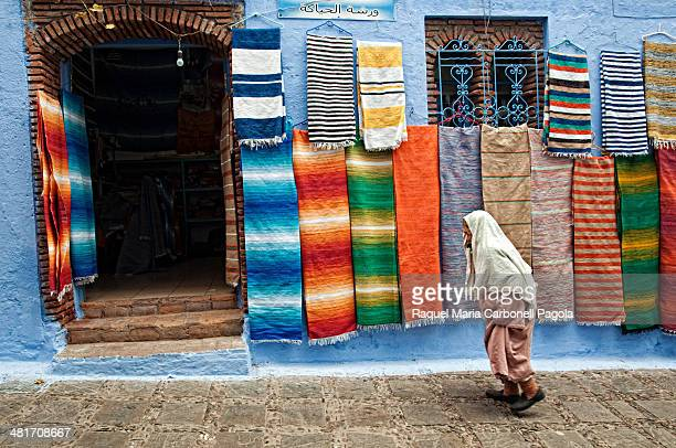 Man in djellaba passing by textile shops in the blue medina
