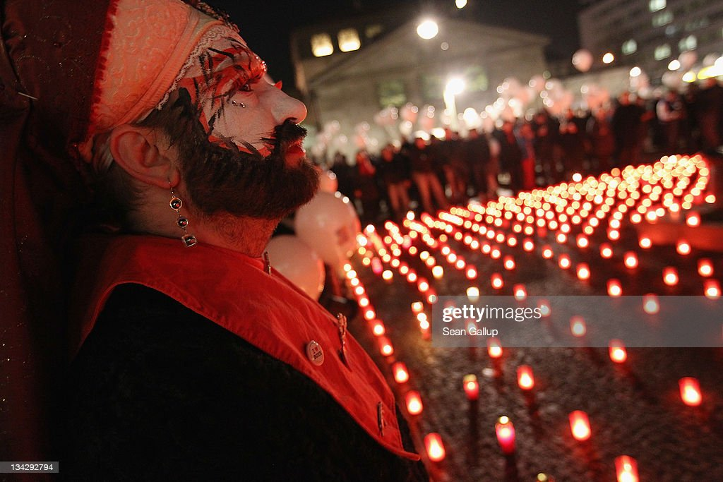 A man in drag watches as participants prepare to release balloons while standing next to a sea of candles at the conclusion of a march to mourn the victims of AIDS on November 30, 2011 in Berlin, Germany. Several hundred people, mostly members of the city's gay community, participated in the march one day ahead of World AIDS Day.