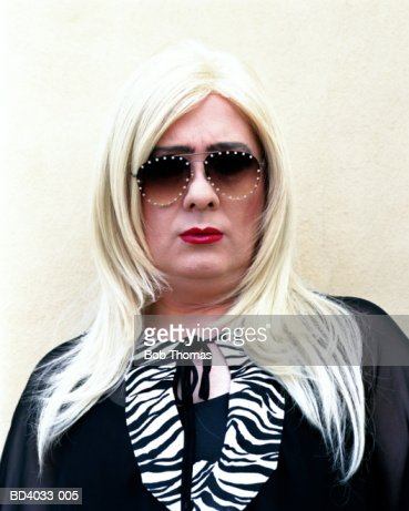Man in drag, wearing blonde wig and sunglasses, portrait