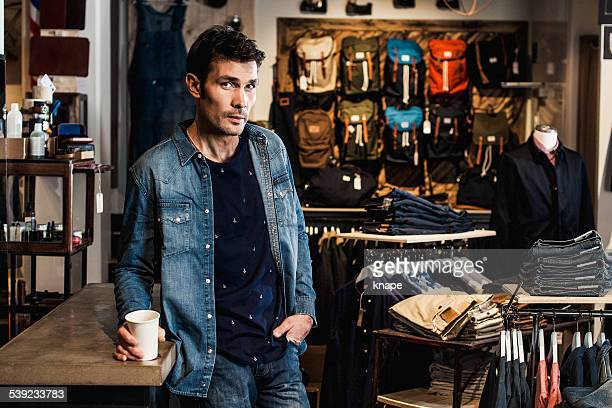 Man in drinking coffee inside a fashion store