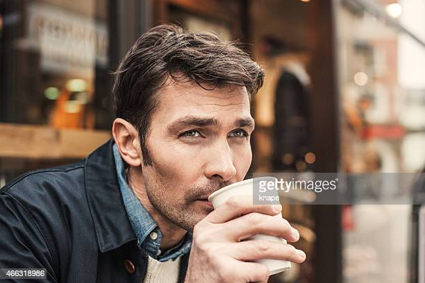 Man in drinking coffee outisde a cafe shop