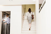 Man in elevator, woman walking up stairs