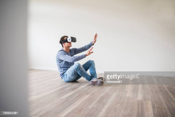 Man in empty apartment wearing VR glasses