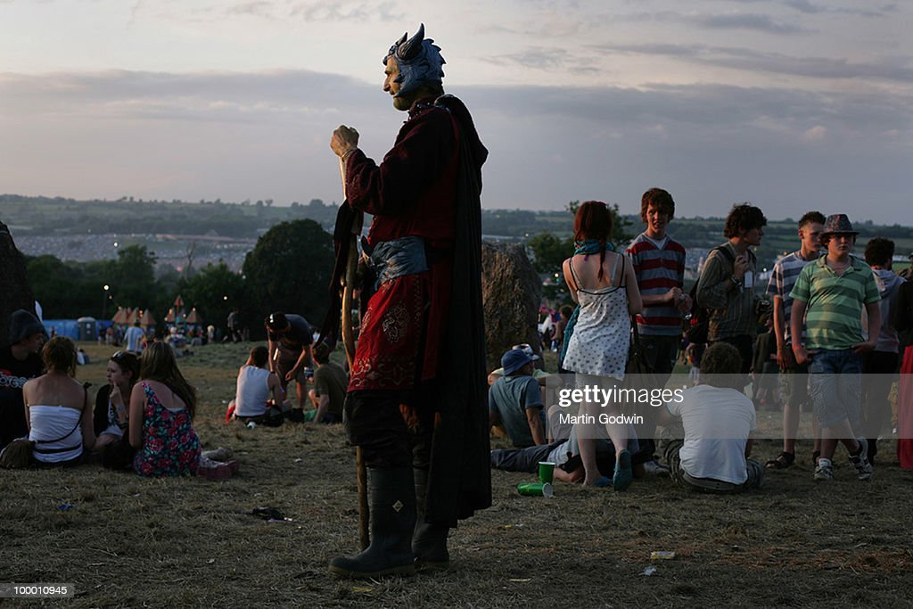 Man in fancy dress with horns and staff at the stone circle as the sun goes down over Glastonbury, 27th June 2009.