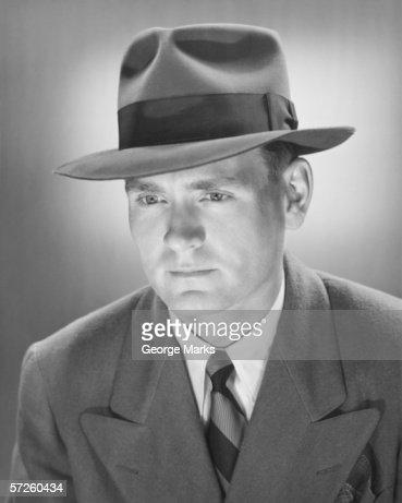 Man in Fedora hat in studio, (B&W), close-up, portrait