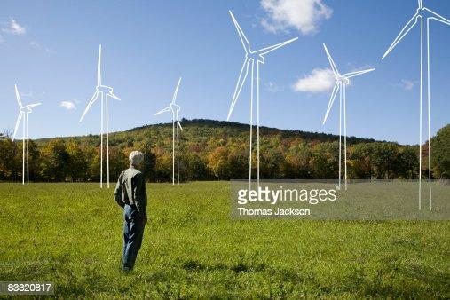 Man in field admiring imaginary wind turbines : Stock Photo