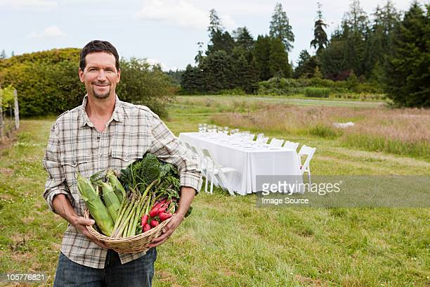 Man in field with basket of produce and table in background