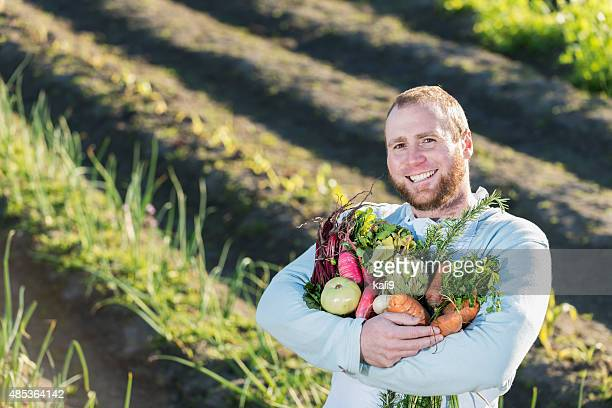 Man in field with bountiful harvest of vegetables