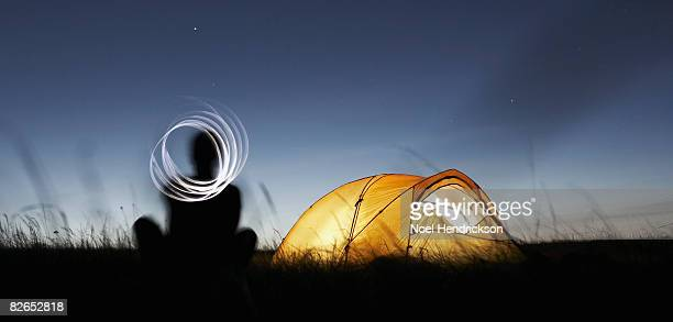 man in field with tent at night