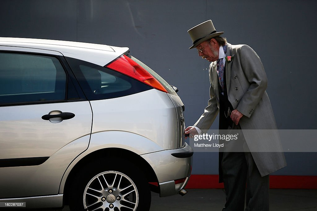 A man in formal attire unlocks his car in the Guildhall Yard on September 29, 2013 in London, England. The Harvest Festival features dancing and entertainment by participants in traditional costumes and concludes with a service at St Mary-le-Bow Church, home of the renowned Bow Bells. Dressing as a Pearly King or Queen, by wearing clothes adorned with pearl buttons, originated in the 19th century when London street sweeper Henry Croft decorated his uniform and began collecting money for charity