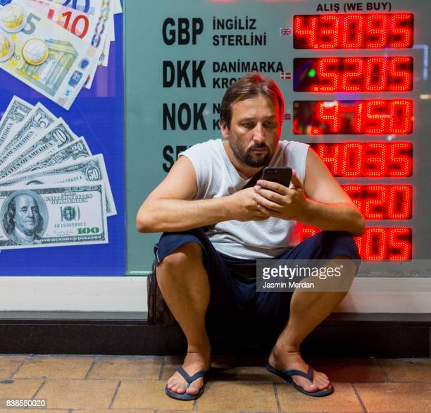 Man in front of bank office using his phone