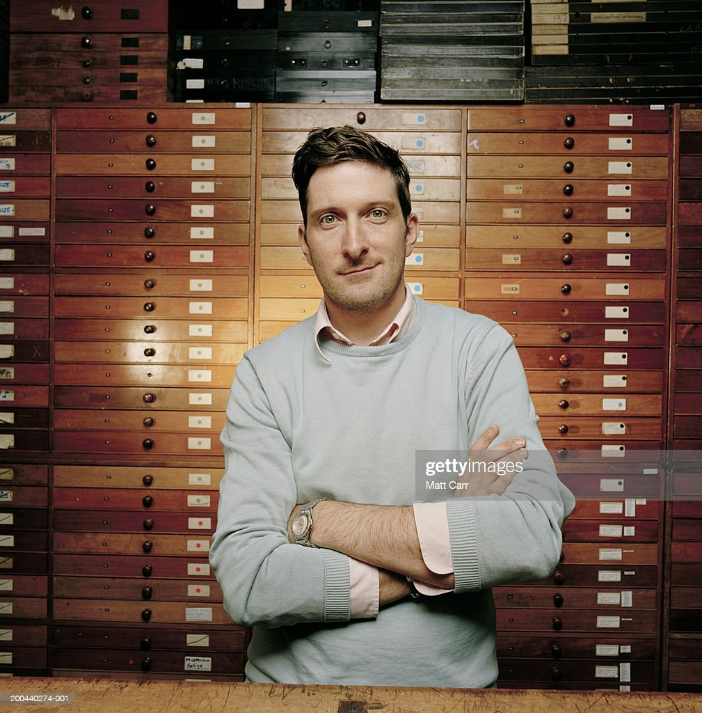 Man in front of flat wooden cabinets for specimens, portrait : Stock Photo