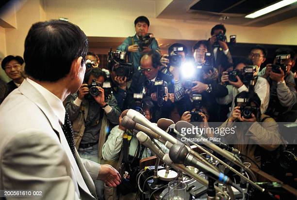Man in front of microphones, surrounded by group of photographers