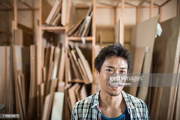 A man in front of shelves of wood