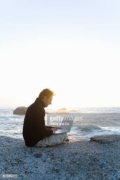 man in front of the sea with his computer