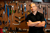Man in front of wall of tools in workshop