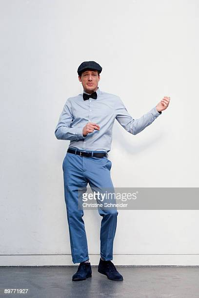 man in front of white wall dancing