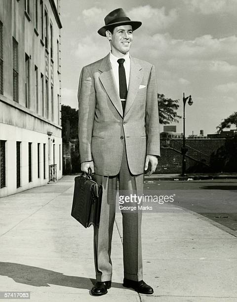 Man in full suit standing on sidewalk, (B&W), (Portrait)