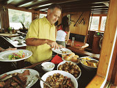 Man in galley of boat, putting food on plate from buffet table