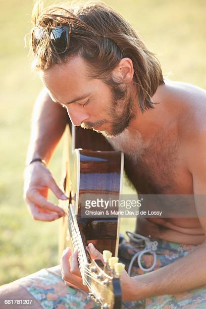 Man in garden playing acoustic guitar, Buonconvento, Tuscany, Italy
