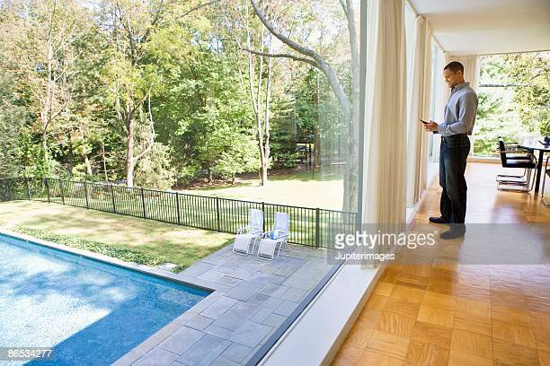 Man in glass house with cell phone