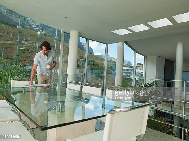 Hombre en vidrio con taza de café y periódico con la naturaleza