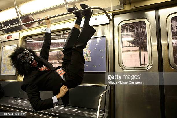 Man in gorilla mask swinging from bars on train