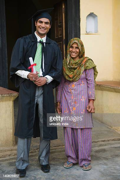 Man in graduation gown holding a diploma and standing with his mother, Hasanpur, Haryana, India