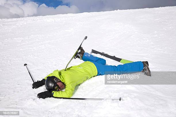 Man in green jacket lying on snow after skiing accident
