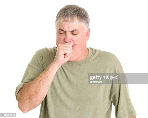 Man in green shirt coughing into his fist
