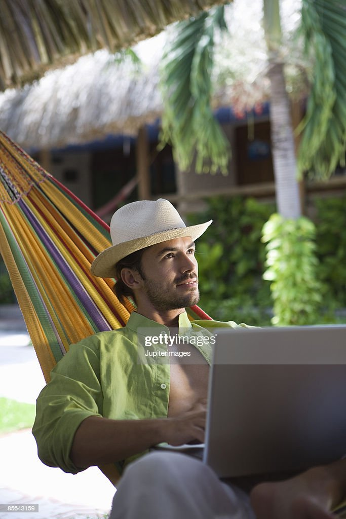 Man in hammock using laptop computer : Stock Photo