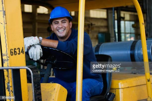 Man in hard hat driving warehouse equipment