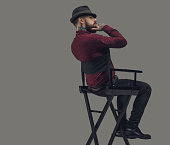 Man in hat sitting on film director's chair. Isolated on grey background.