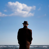 Man in hat staring at the sea
