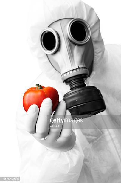 Man in hazmat suit holding a tomato