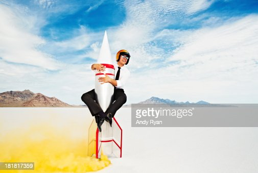 Man in helmet astride rocket about to take off.