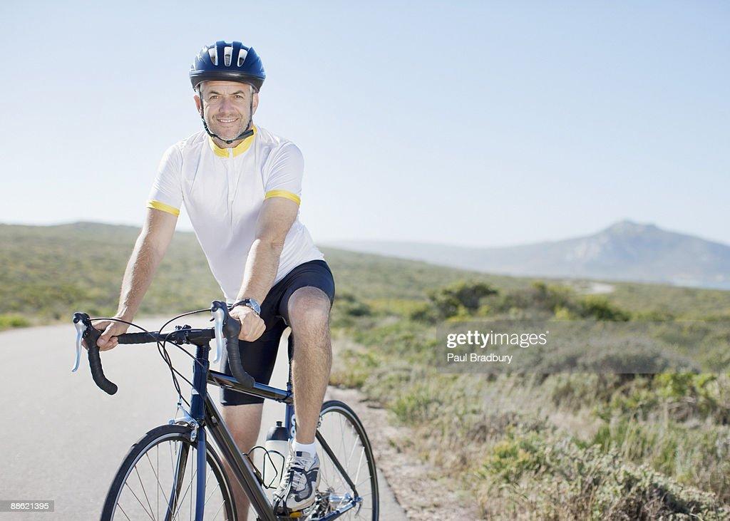 Man in helmet sitting on bicycle : Stock Photo