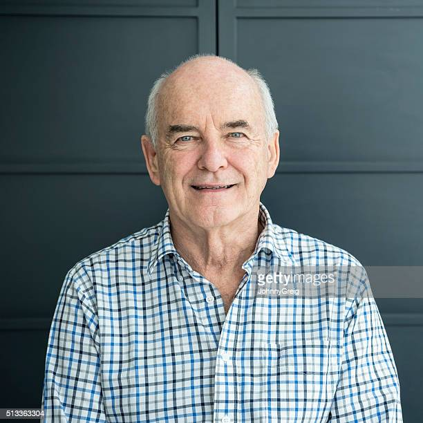 Man in his 70s smiling at camera against grey background