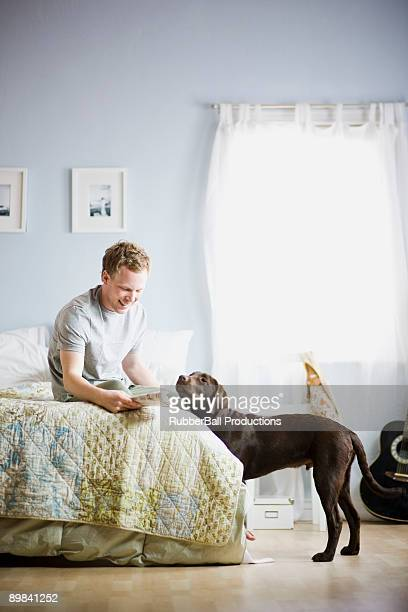 man in his bedroom with his dog