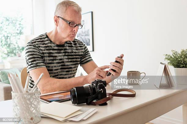 Man in home office using smartphone