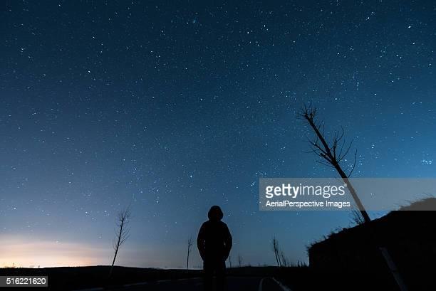 A man in hood against starry sky