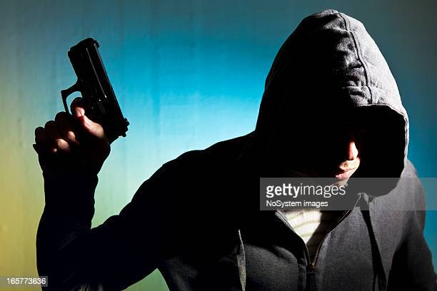 Man in hood with revolver