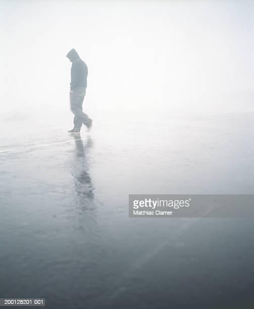 Man in hooded jacket crossing road in rain, side view (blurred motion)