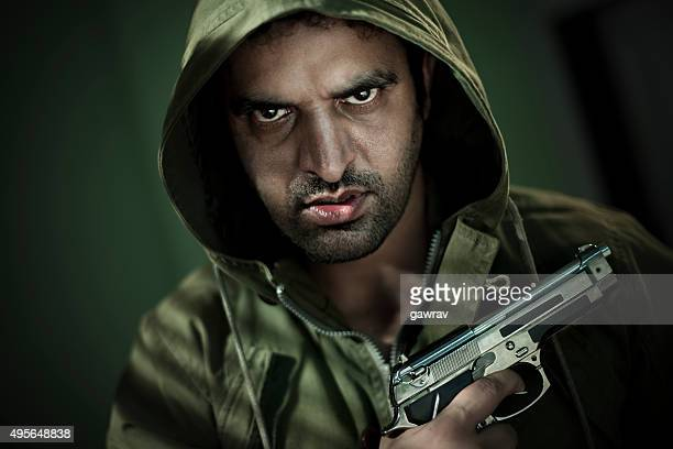 Man in hoodie jacket with a gun and sharp gaze.