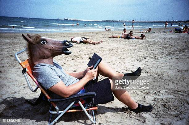 Man in horse head reading book on beach