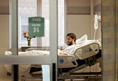 Man in hospital bed drinking from styrofoam cup