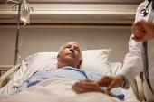 Man in hospital bed having pulse taken